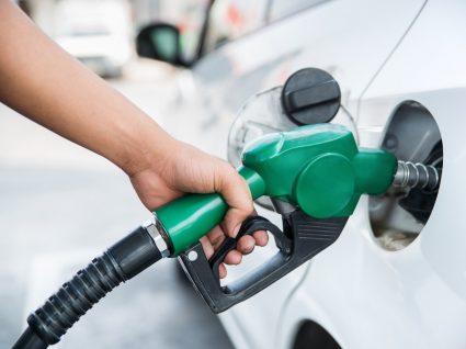 pessoa a abastecer carro do lado da porta do tanque do combustível