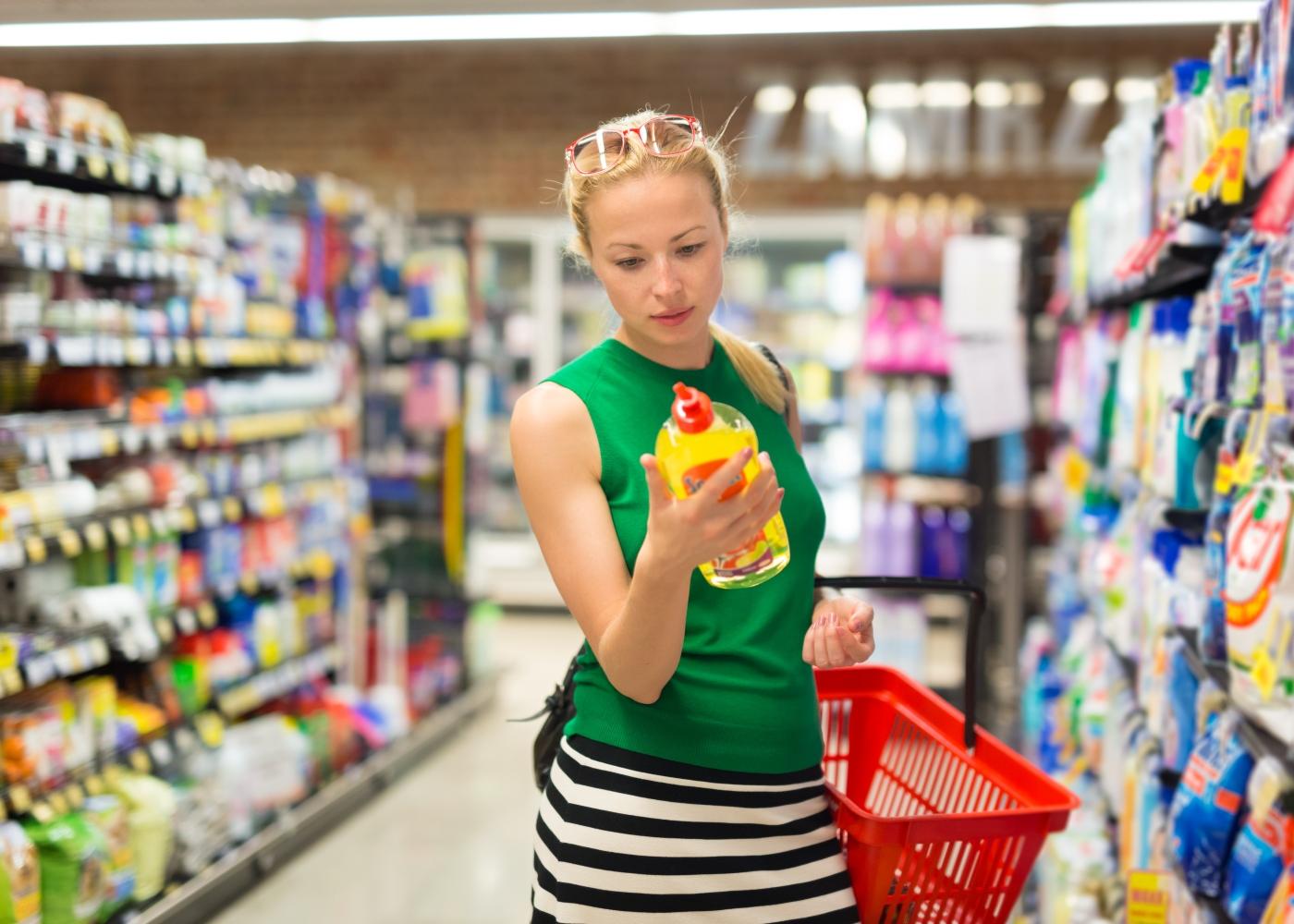 mulher a escolher detergente ecológico no supermercado
