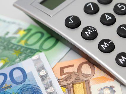 máquina de calcular e dinheiro em cima de uma mesa