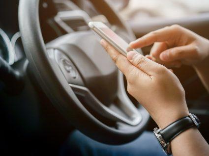 condutor no carro a procurar apps que mostram preços de combustível