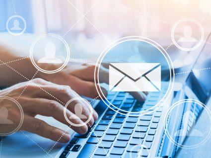 mãos no teclado de um computador e vários emojis de email e conteividade de pessoas