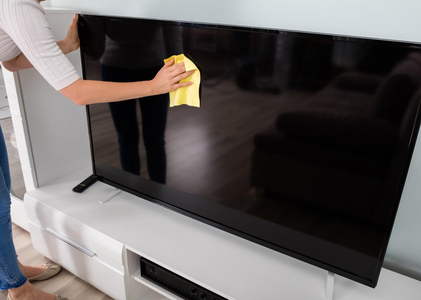 pessoa a limpar ecrã da televisão com um pano e não vinagre
