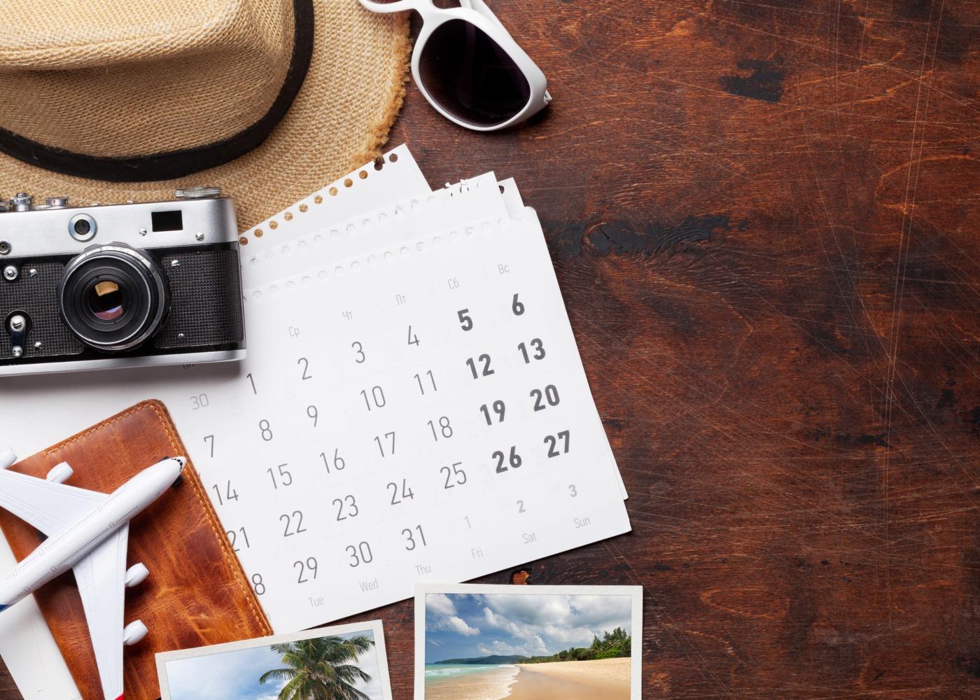 calendário, chapéu, avião e máquina fotográfica dispostos numa mesa