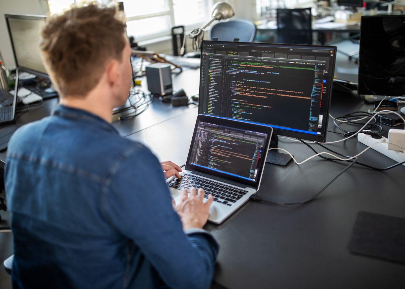 programador a trabalhar com dois ecrãs