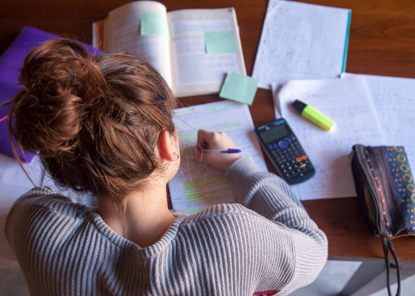 vista de cima de uma jovem a estudar com livros, calculadora e outros materiais vários