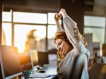 mulher em frente ao computador a fazer alongamentos como um dos exercícios para fazer no escritório
