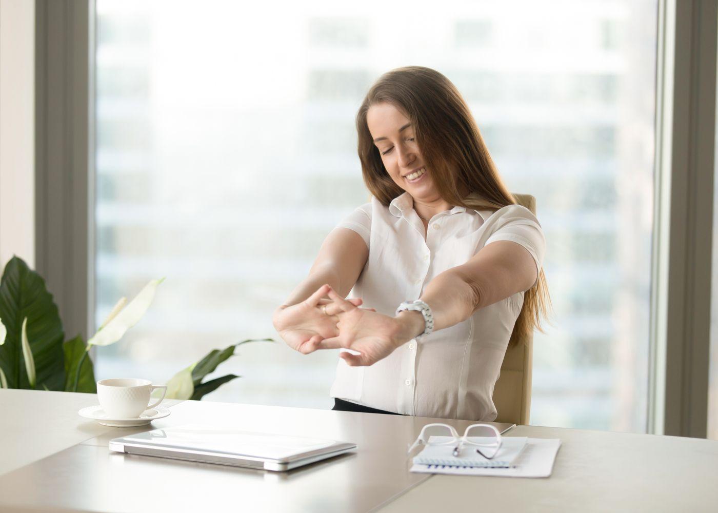 mulher a alongar os braços no escritório