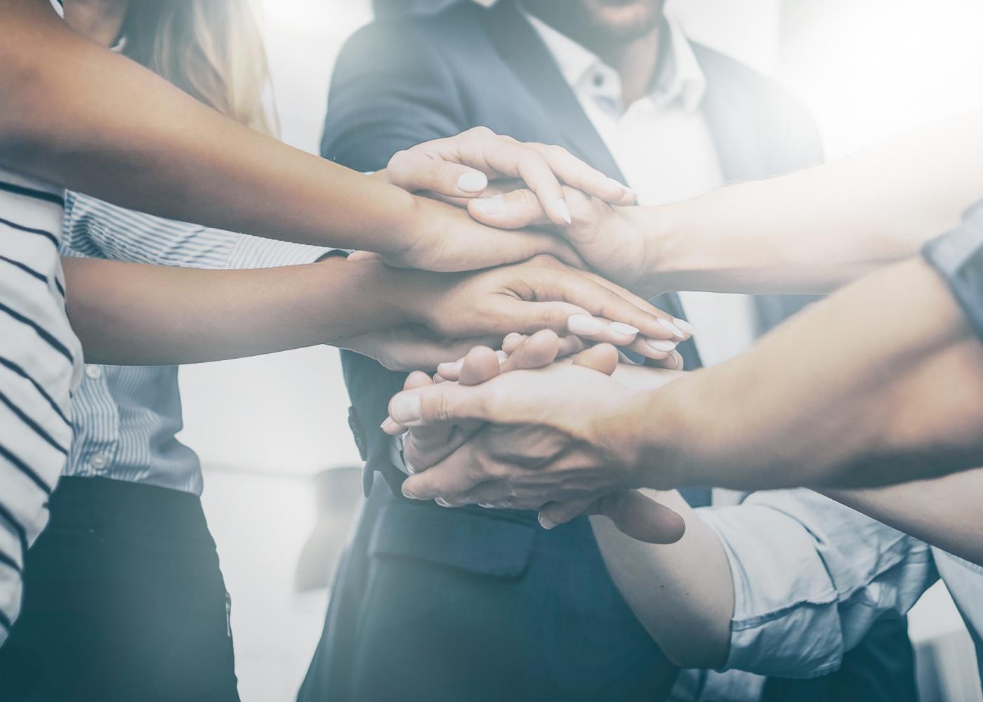 equipa com mãos ao centro como forma de união