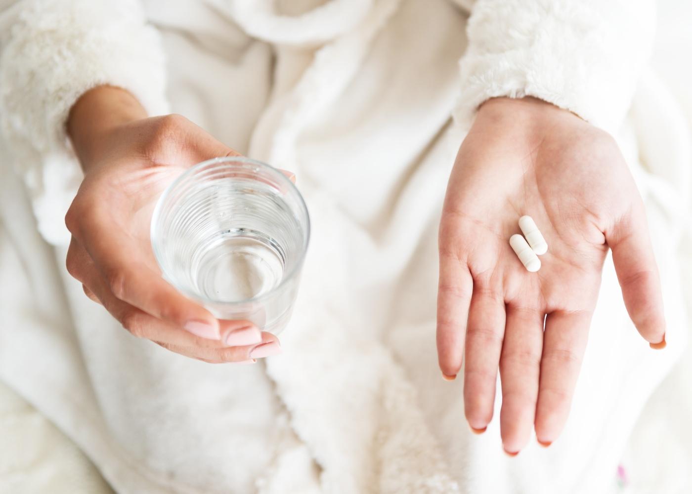 mulher com medicamentos na mão para tomar