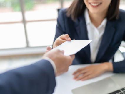 chefe a dar envelope com vencimento a funcionária