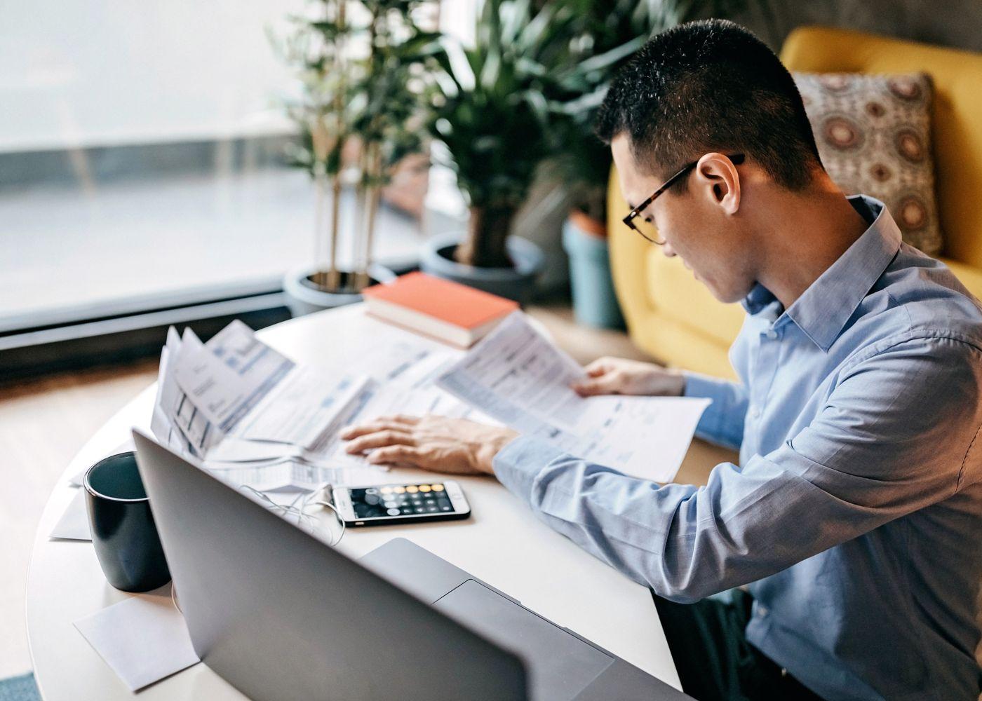 jovem a trabalhar com computador e documentos