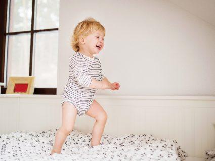 criança feliz a saltar na cama