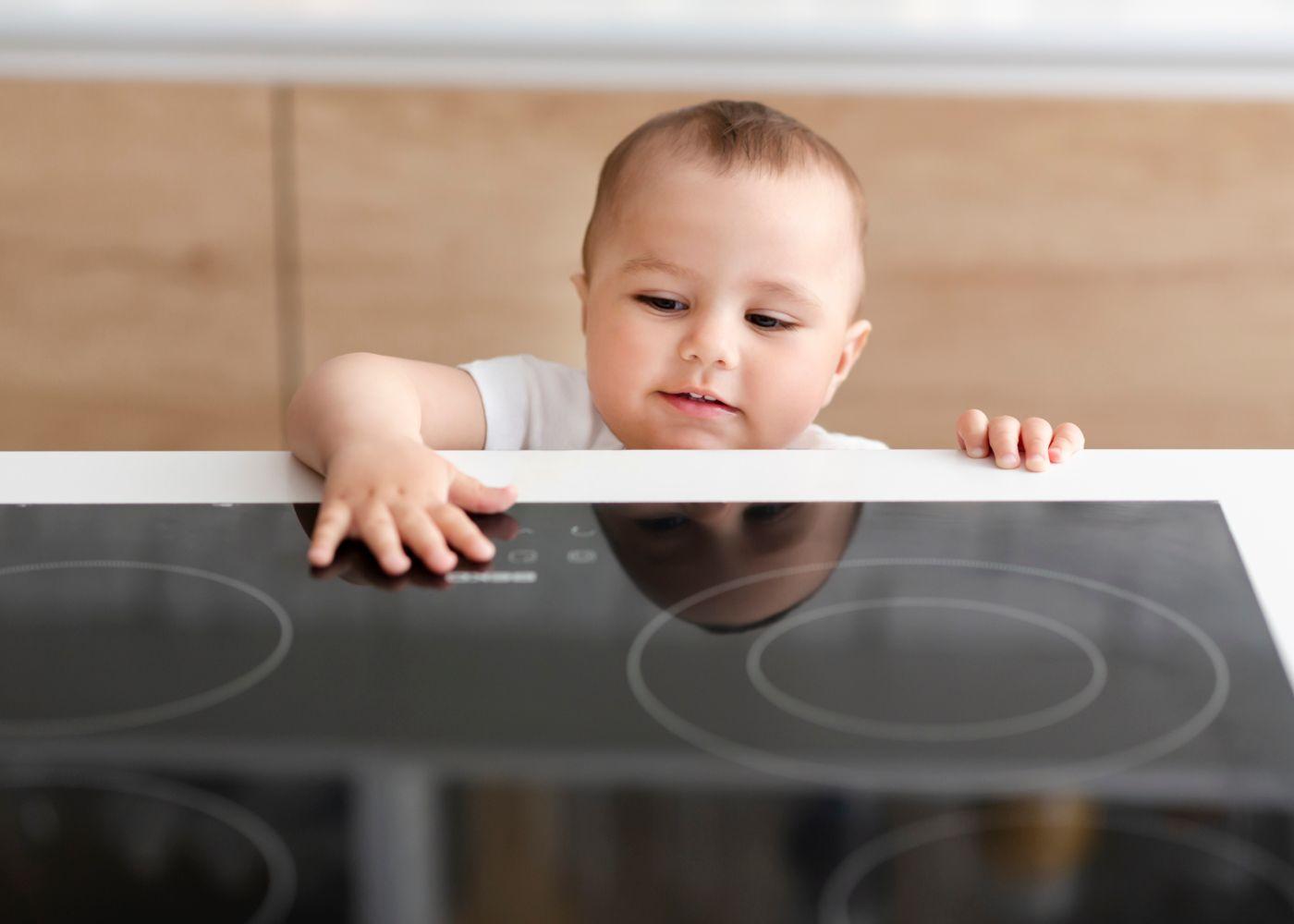 bebé com as mãos na placa para mostrar importância de uma casa segura para crianças