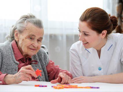 cuidadora a ajudar idosa com puzzle