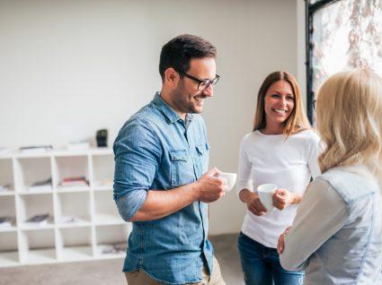 três colegas a conversar e a tomar café