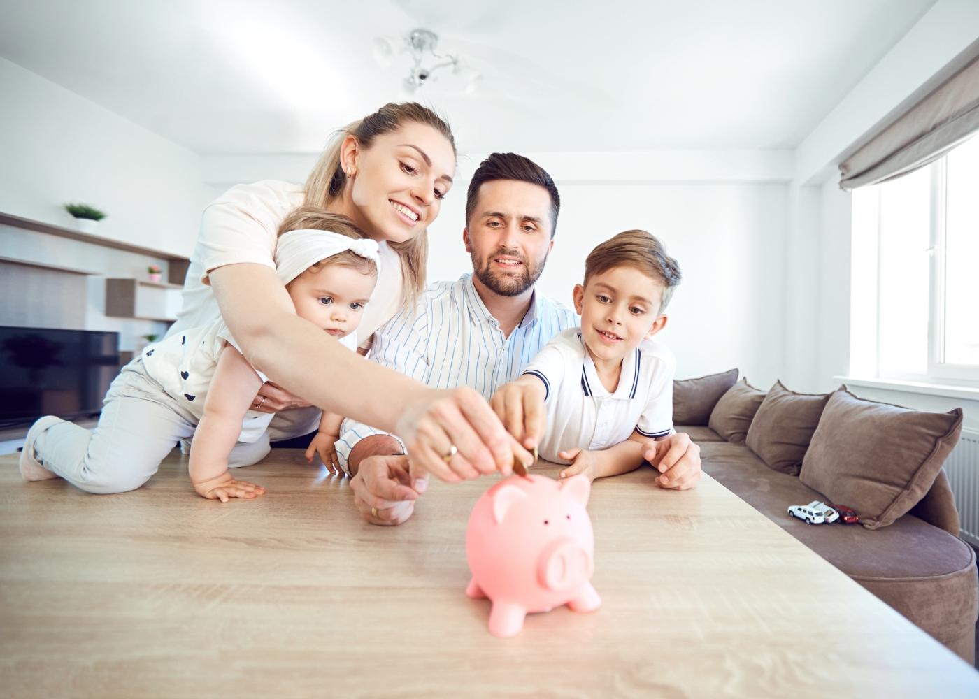 Pais e filhos a colocar moedas num mealheiro