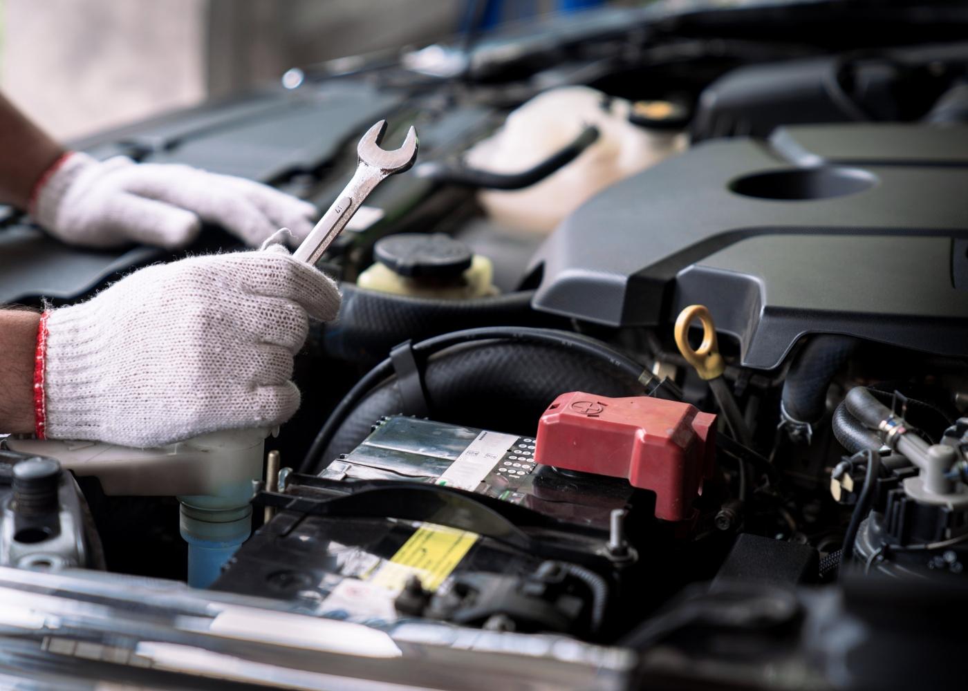 mecânico a analisar sinais de que a bateria do carro está fraca