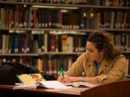 estudante com bolsa de estudo a estudar na biblioteca