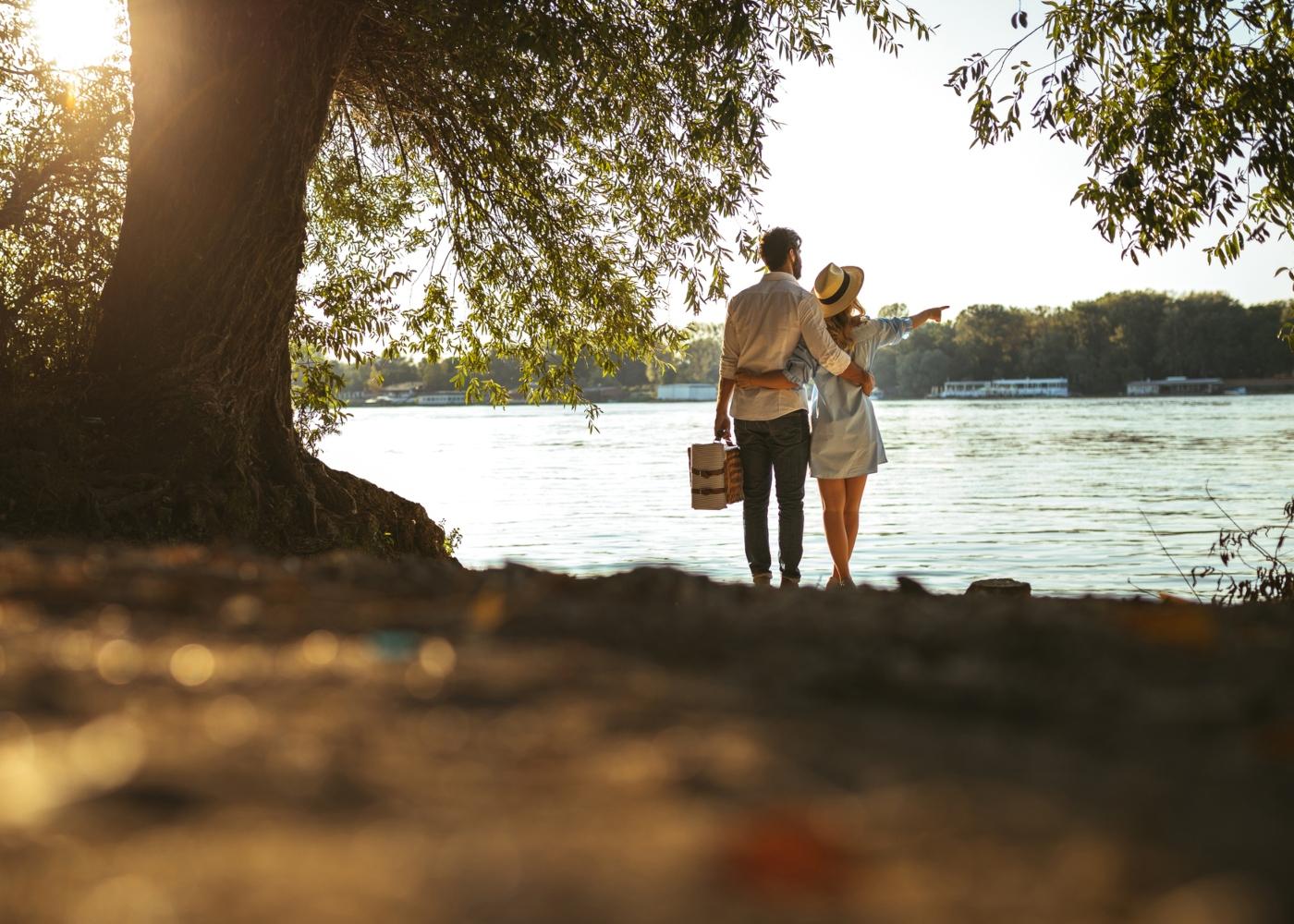 Casal a fazer um piquenique junto a praia fluvial