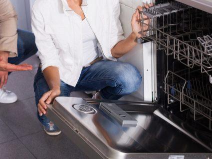 duas pessoas a ver interior da máquina de lavar a loiça