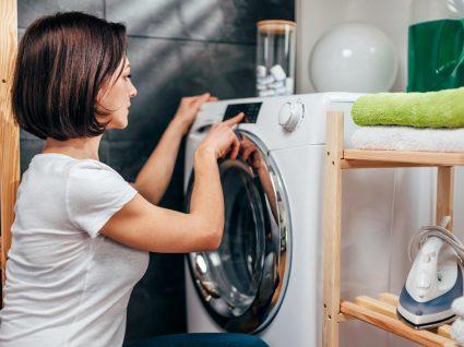 mulher a por roupa a secar na máquina