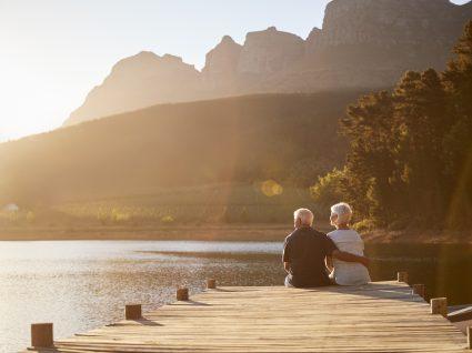 casal idoso sentado num passadiço a ver o rio