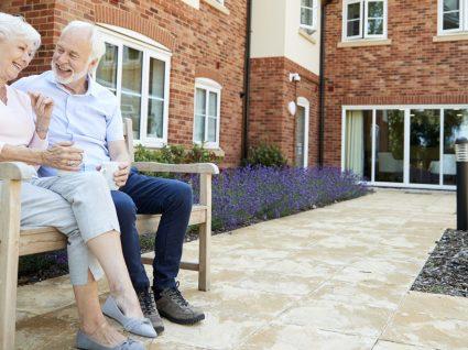 casal de pensionistas sentados num banco de jardim