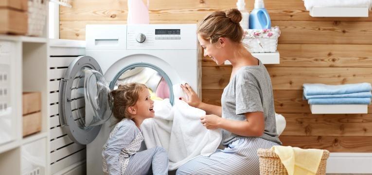 mãe e filha a por roupa branca na máquina de lavar a roupa