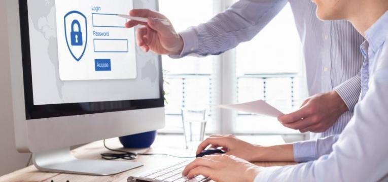 duas pessoas a olhar para o ecrã do computador