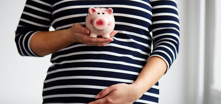 mulher grávida segurando um mealheiro