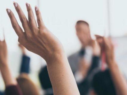 mãos levantadas para tirar dúvidas em formação