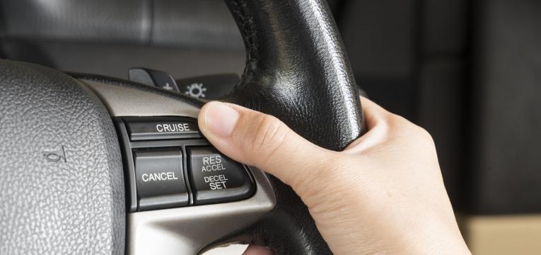 condutor a ativar o cruise control