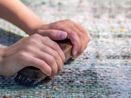 pessoa a escovar um tapete