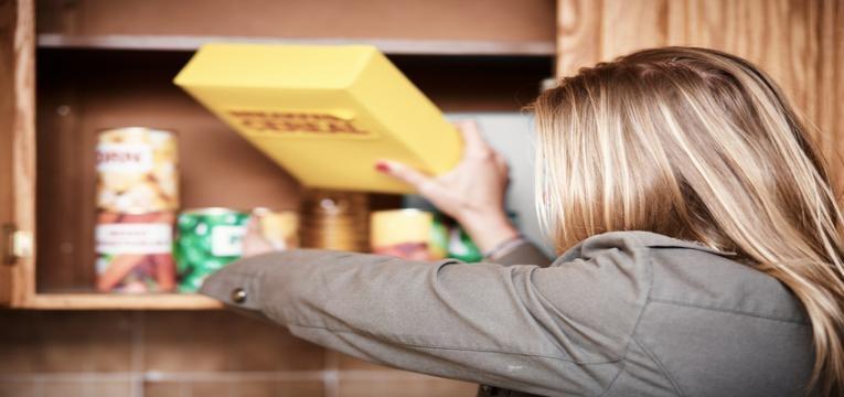 mulher a retirar produtos da despensa