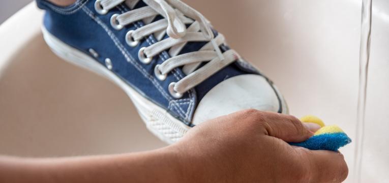 pessoa a lavar sapatilhas à mão