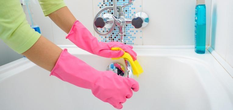 mulher a limpar torneira da banheira