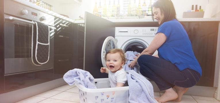 mãe a por a roupa na máquina com bebé no cesto