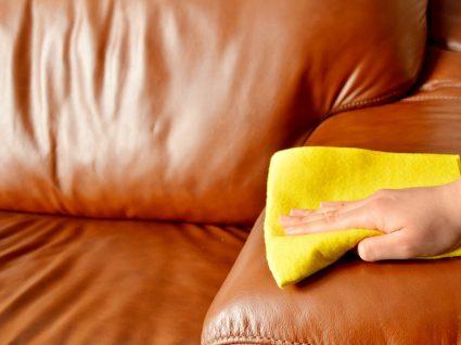 pessoa com pano amarelo a limpar sofá castanho de cabedal