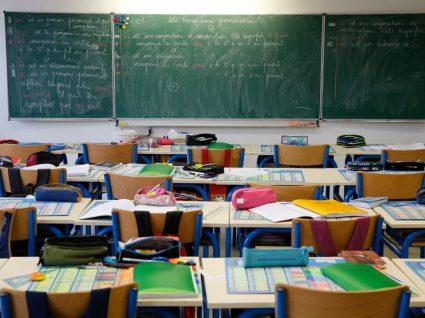 sala de aula vazia com materiais de alunos beneficiários de ação social escolar