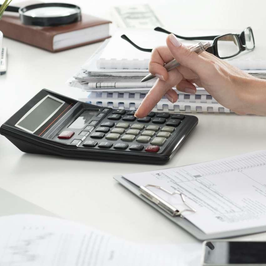 mãos seguram óculos e usam calculadora