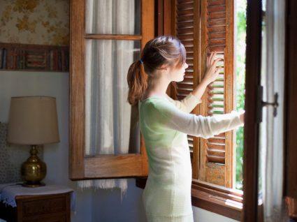 mulher a abrir a janela para arejar a casa