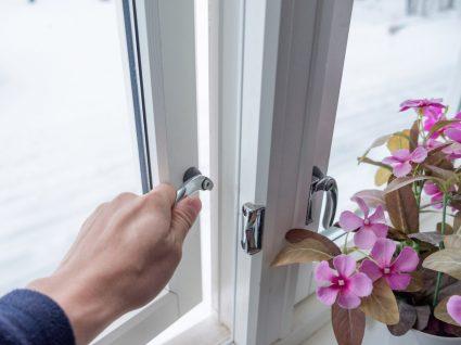 pessoa a abrir a janela para manter a casa fresca em dias quentes