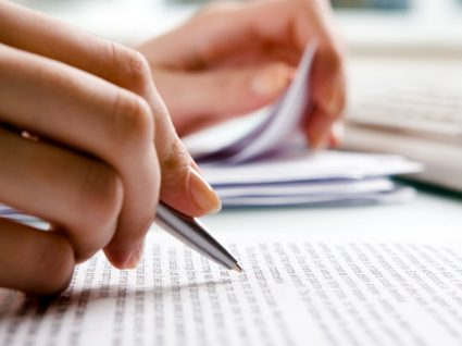 pessoa a ler documento com caneta na mão para anotações