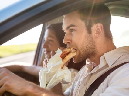 Comer a conduzir dá multa?