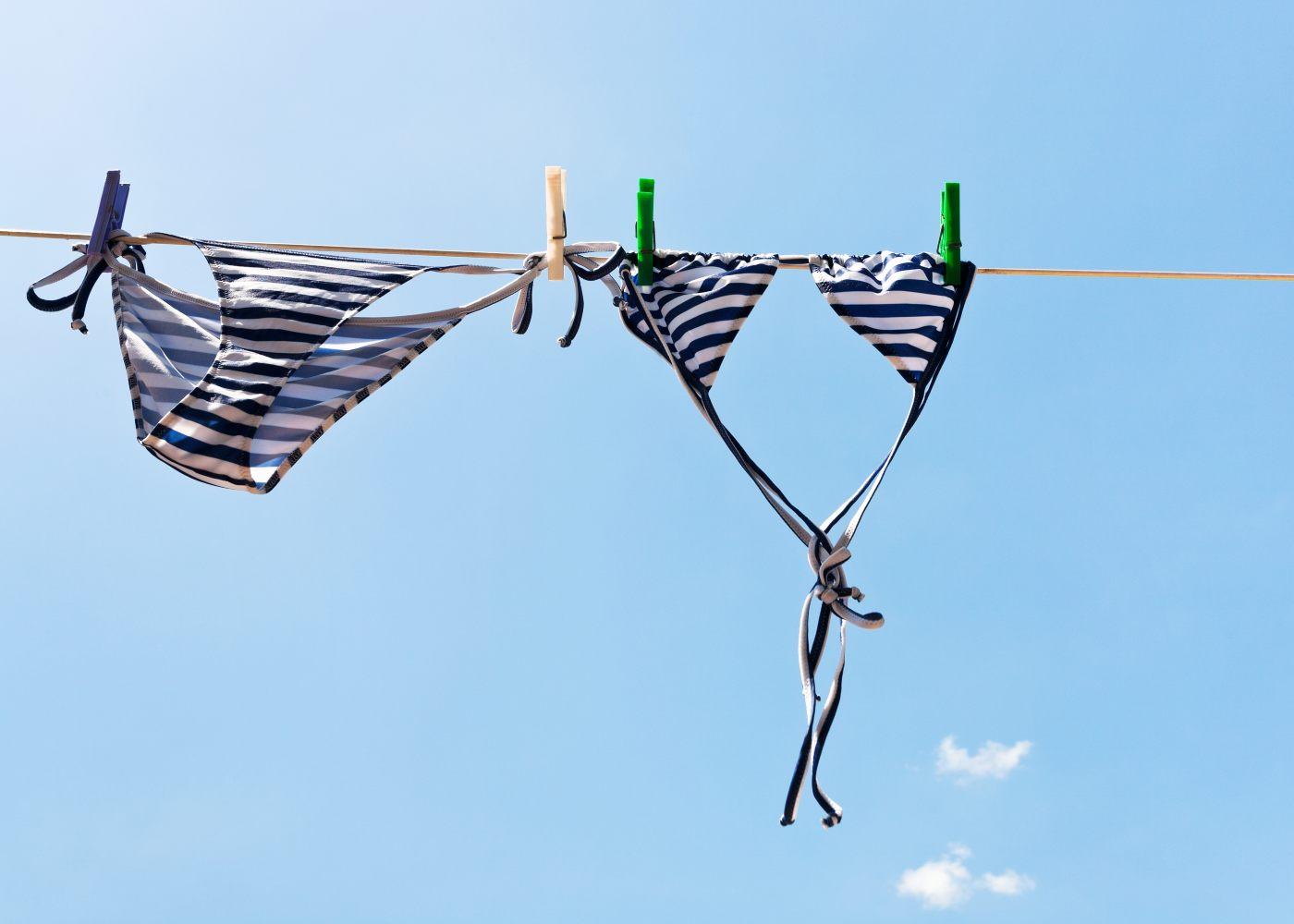 biquini a secar numa corda depois de pessoa consultar como lavar os fatos de banho