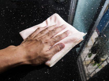 pessoa com um pano a ver como limpar superfícies de mármore