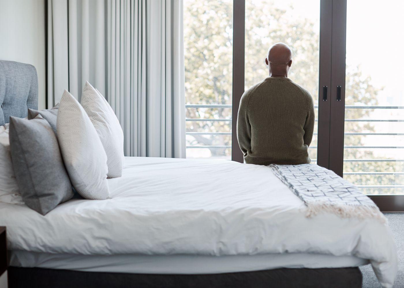 homem sentado na cama a olhar pela janela