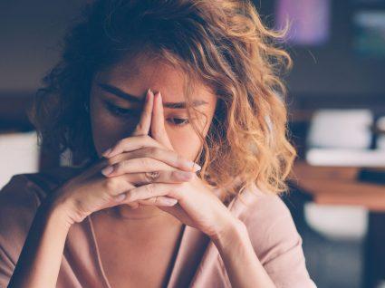 mulher com mãos na cara a sofrer de depressão de domingo