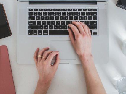 mãos de mulher ao computador com telefone e agenda ao lado