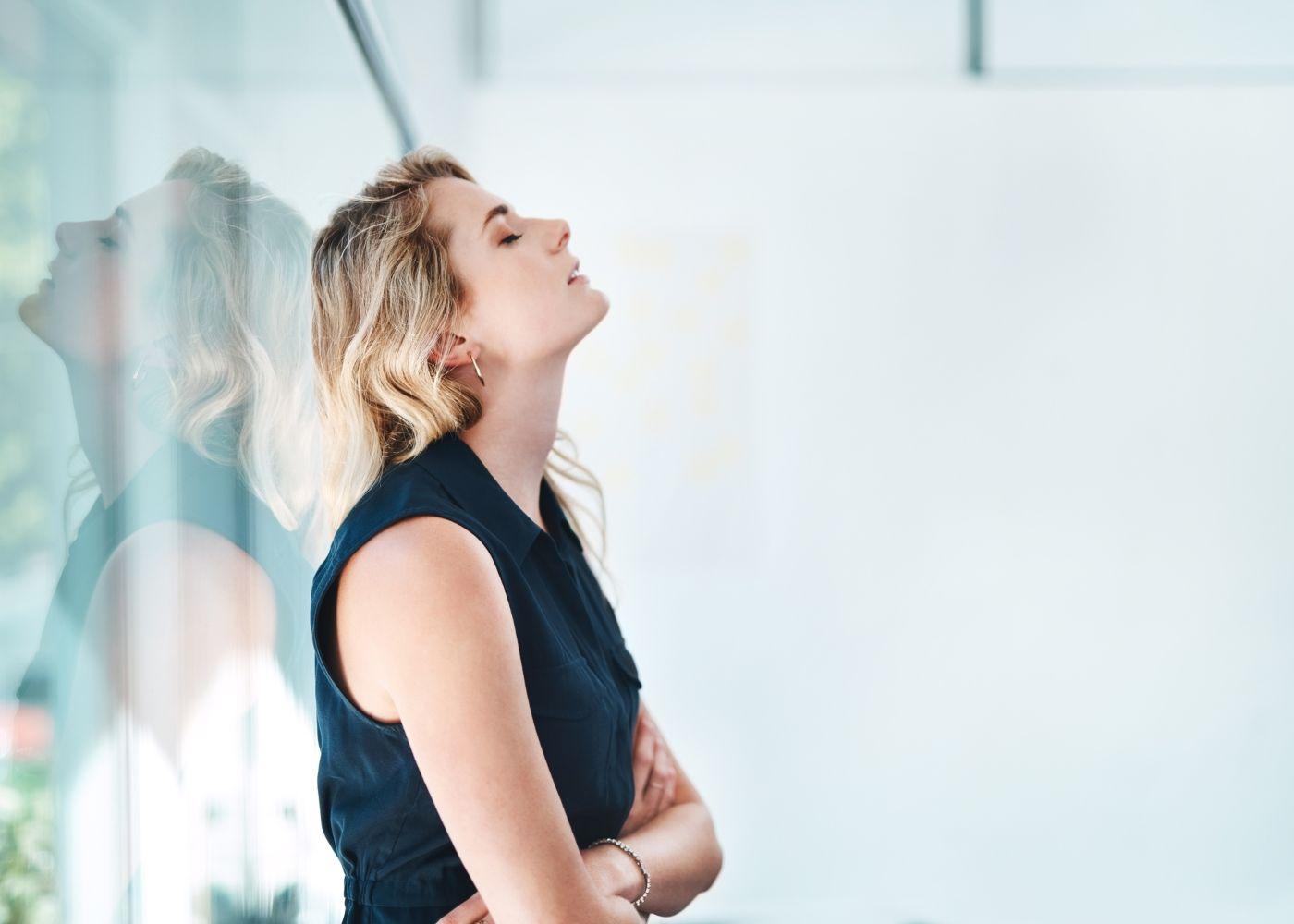 mulher encostada a mostrar sinais de desmotivação no trabalho
